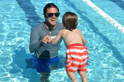swim instructor with toddler in water